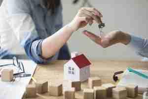 mujer dando llave de vivienda a hombre
